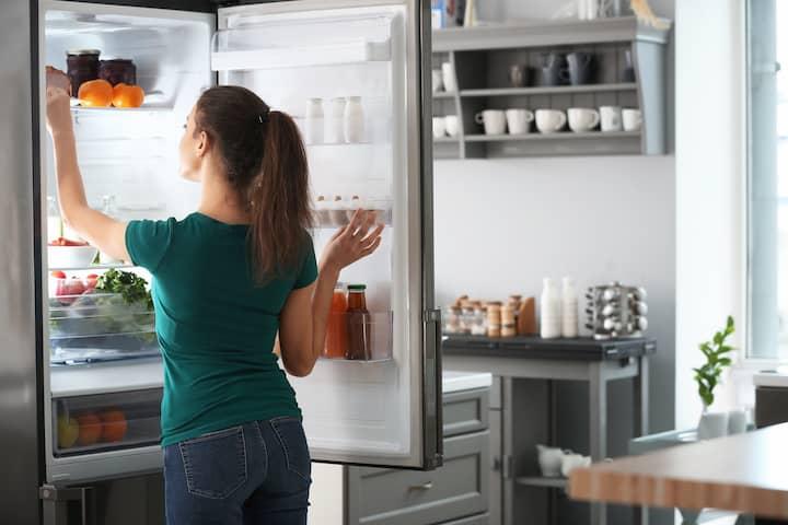 Vrouw bij goedkope koelkast